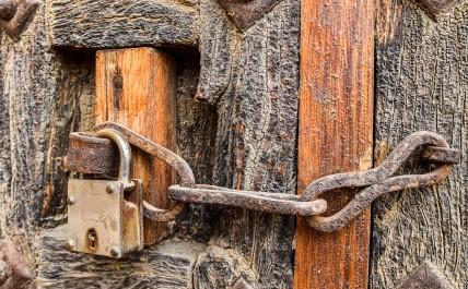 Old styled rusty chain door lock on the wooden door