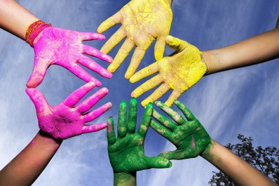 Young people hands covered in Holi Colors under blue sky
