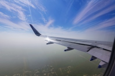 View through the window of a passenger plane flying above the city