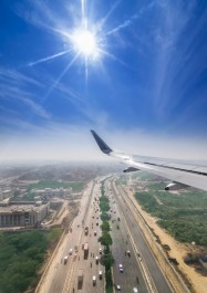 View through the window of a passenger plane flying above Delhi Gurgaon highway